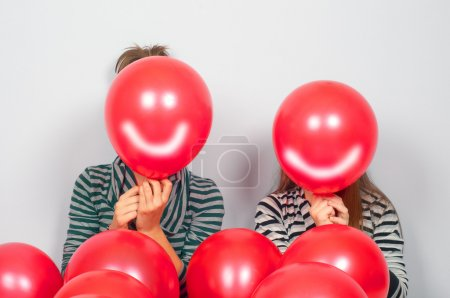 Photo for Teenage girls hiding their faces behind smiling balloons - Royalty Free Image
