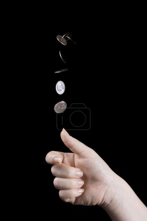 Photo for Multiple exposure image of hand flipping a coin on black background - Royalty Free Image