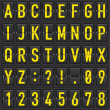 Set of yellow letters on a mechanical timetable. I...