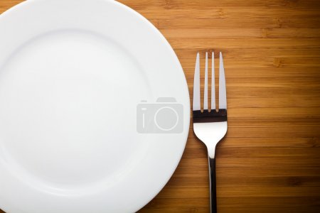 Photo for Empty plate and fork on wood table - Royalty Free Image