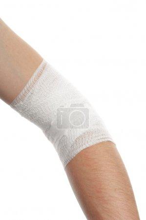 Photo pour Bandage médical blanc sur coude blessé sur fond blanc - image libre de droit