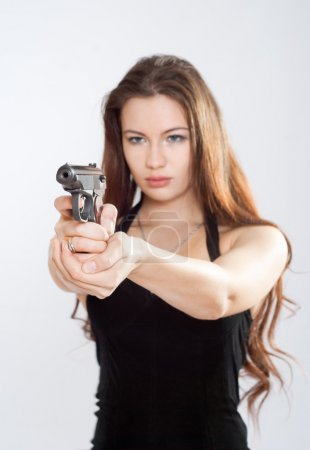 Photo for Girl aiming a gun, arms outstretched - Royalty Free Image