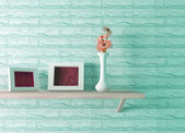 Ceramics vase with flower and two picture frames on the shelf