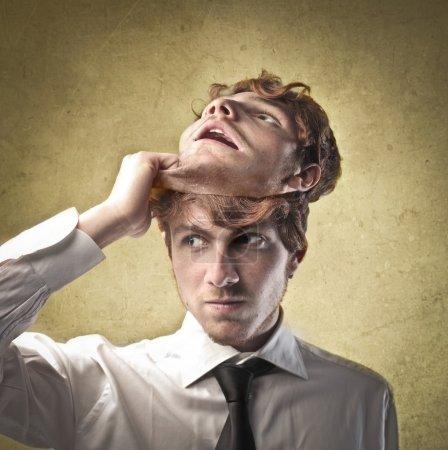 Photo pour Jeune homme d'affaires qui décollait un masque de lui-même - image libre de droit