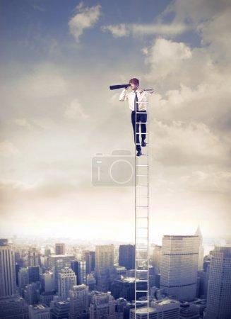 Photo pour Jeune homme d'affaires sur une échelle au cours d'une grande ville et à l'aide d'un télescope - image libre de droit