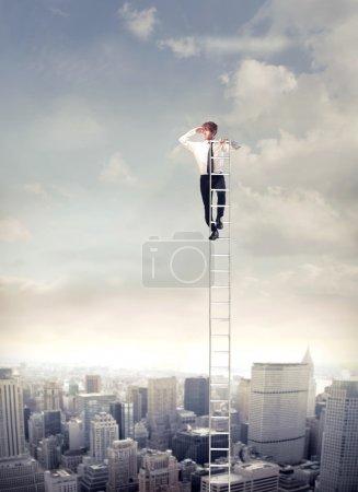 Foto de Joven empresario en una escalera sobre una gran ciudad mirando lejos - Imagen libre de derechos