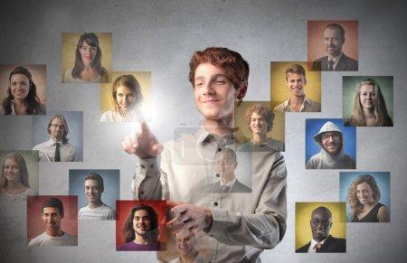 Photo pour Souriant jeune homme d'affaires touchant des icônes de divers - image libre de droit