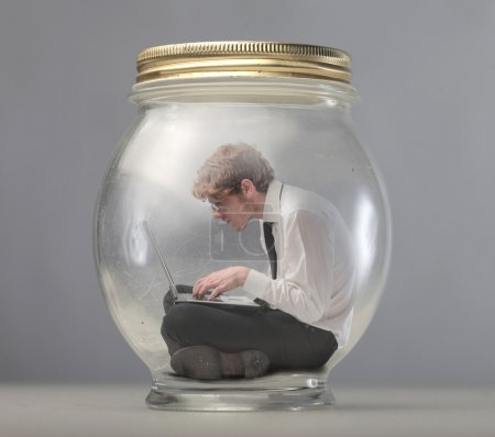 Photo for Young businessman trapped in a glass jar and using a laptop - Royalty Free Image