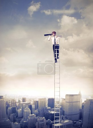 Photo for Young businessman on a ladder over a big city using a telescope - Royalty Free Image
