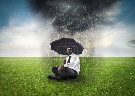 Photo for African businessman sitting on a green meadow under an umbrella with stormy sky above him - Royalty Free Image