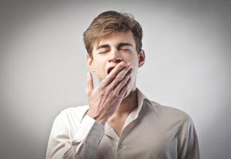 Young man yawning