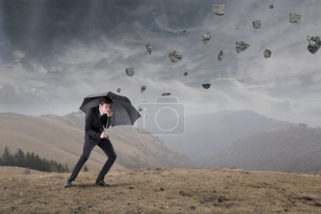 Photo for Businessman sheltering under an umbrella from rocks falling to the ground - Royalty Free Image