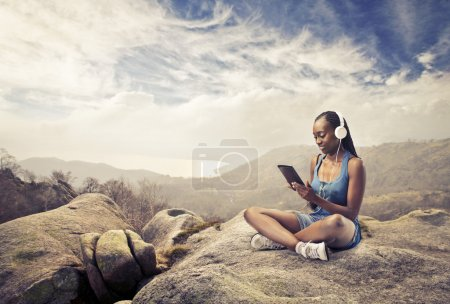 Smiling african woman sitting on a rock and using a tablet pc