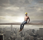 Young brawny worker sitting on a metal bar over a big city