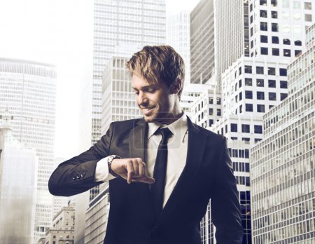 Smiling young businessman looking at his wristwatch with cityscape in the background