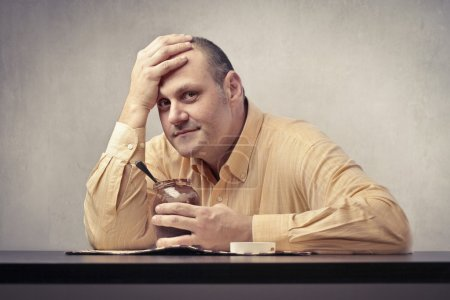 Photo for Worried fat man holding a pot of chocolate cream - Royalty Free Image