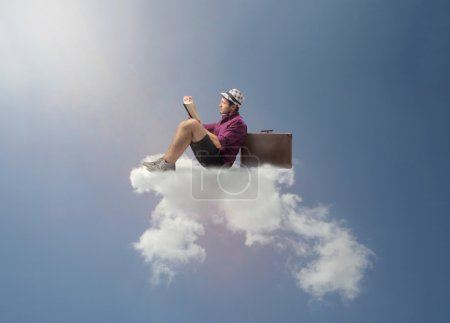 Photo for Young touristi sitting on a cloud and reading a book - Royalty Free Image