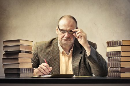 Photo pour Professeur sévère à son bureau entouré de livres et de feuilles de papier - image libre de droit