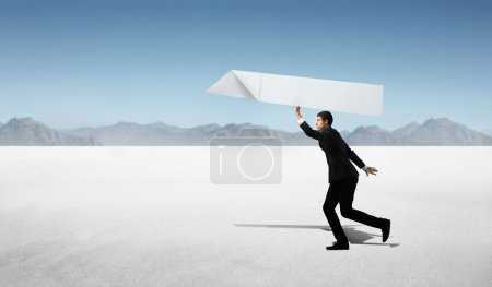 Photo for African businessman throwing a model airplane in a desert - Royalty Free Image