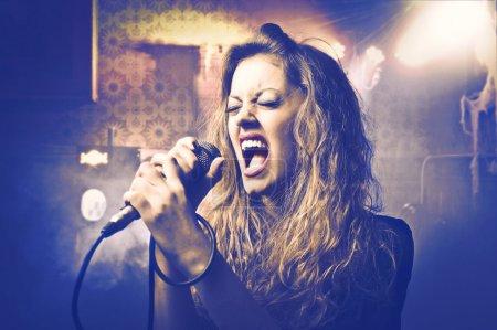 Photo pour Belle femme chantant dans un micro - image libre de droit