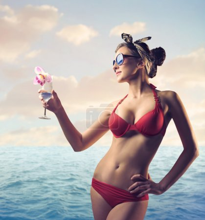 Photo for Beautiful woman in bathing suit holding a cocktail at the seaside - Royalty Free Image
