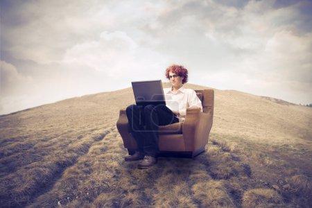 Photo pour Homme d'affaires assis sur un fauteuil sur une colline et à l'aide d'un ordinateur portable - image libre de droit