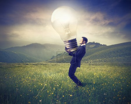 Photo for Businessman lighting up a green meadow with a giant light bulb - Royalty Free Image