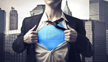 Photo for Businessman showing the superhero suit under his shirt with cityscape in the background - Royalty Free Image