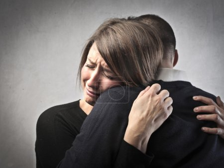 Photo for Crying young woman hugging her husband - Royalty Free Image