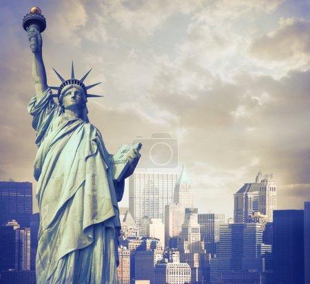 Photo pour Statue de la liberté avec la ligne d'horizon de la ville de new york en arrière-plan - image libre de droit