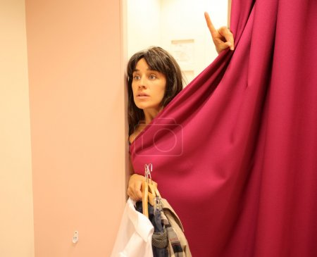 Photo for Beautiful woman asking for clothes from a fitting room - Royalty Free Image