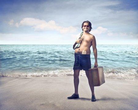 Photo pour Homme souriant en maillot de bain tenant une valise sur une plage - image libre de droit