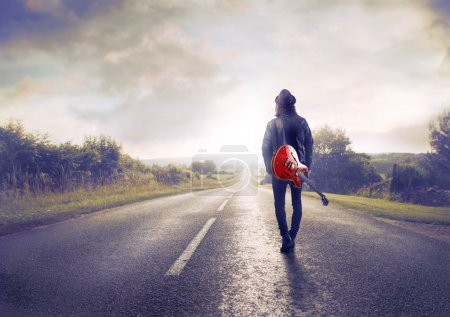 Photo for Young man walking on a country road with a guitar on his shoulder - Royalty Free Image