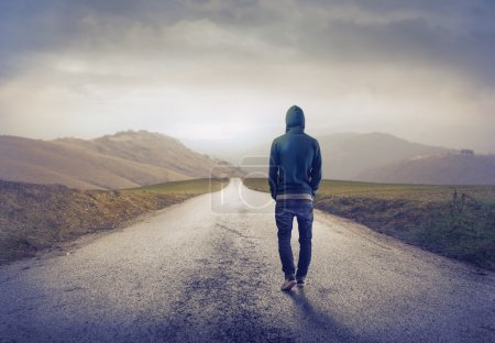 Photo for Young man walking on a country road - Royalty Free Image