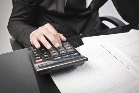 Photo pour Gros plan d'un homme d'affaires utilisant une calculatrice - image libre de droit