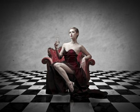 Photo for Beautiful elegant woman sitting on an armchair and having a glass of champagne - Royalty Free Image