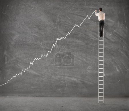 Photo for Young businessman on a ladder charting a positive trend graph - Royalty Free Image