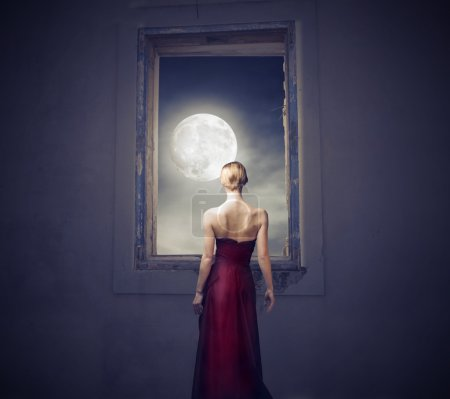 Photo pour Belle femme élégante regardant la lune par la fenêtre d'une chambre - image libre de droit