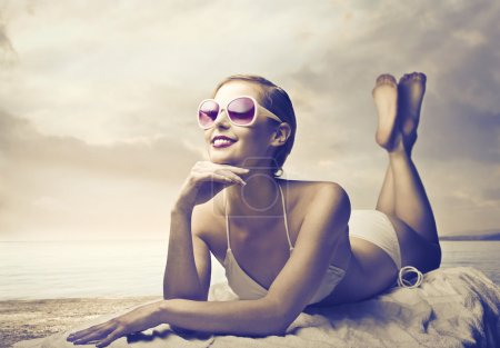 Photo for Smiling beautiful woman in bathing suit lying on a bathtowel at the seaside - Royalty Free Image