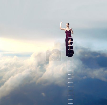 Photo for Beautiful elegant woman on a ladder in the sky drawing - Royalty Free Image