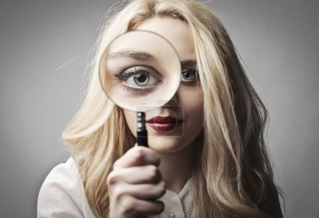 Photo for Young woman holding a magnifying glass - Royalty Free Image