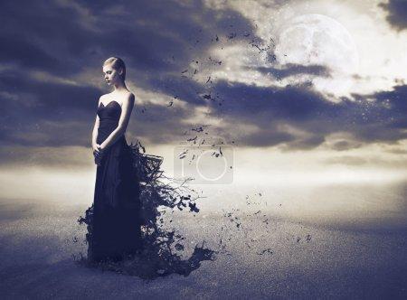 Photo pour Belle femme élégante avec sa robe de soirée déchirant dans le vent - image libre de droit