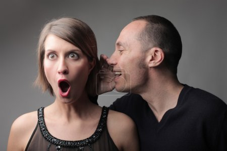 Photo for Man telling an astonished young woman some amazing news - Royalty Free Image