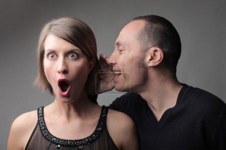 Photo pour Homme en disant à une jeune femme étonnée quelques nouvelles étonnantes - image libre de droit