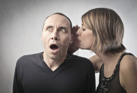 Young woman telling an astonished man some news...