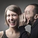 Man telling a laughing woman a joke...