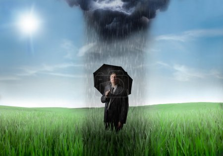 Photo for Sad senior businessman under and umbrella with a raincloud over him and sunny sky in the background - Royalty Free Image