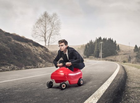 Young businessman driving a toy car on a country r...