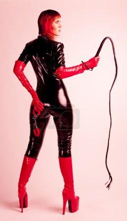 Photo pour Femme debout, portant des vêtements extravagants, tenant un fouet et menottes - image libre de droit