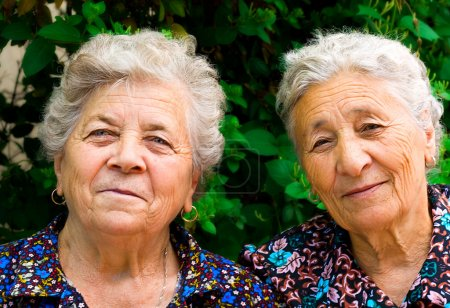 Outdoor portrait of two old ladies...
